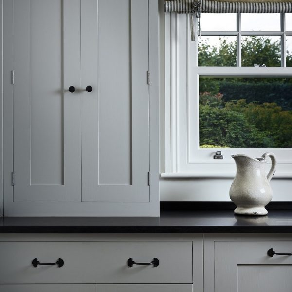 Clocktower painted kitchen cupboard with window to the right and a jug on the kitchen surface