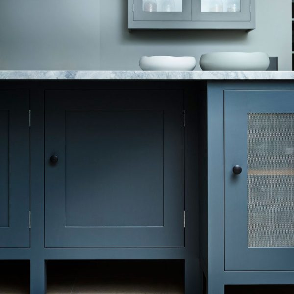 Close up of blue cupboard and marble counter top with white bowls