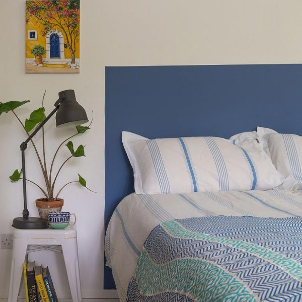 Beb with blue painted headboard, beside table with lamp and plant