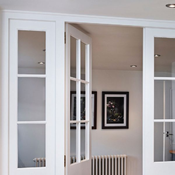 Open indoor glass doors to a warm white painted room with two paintings