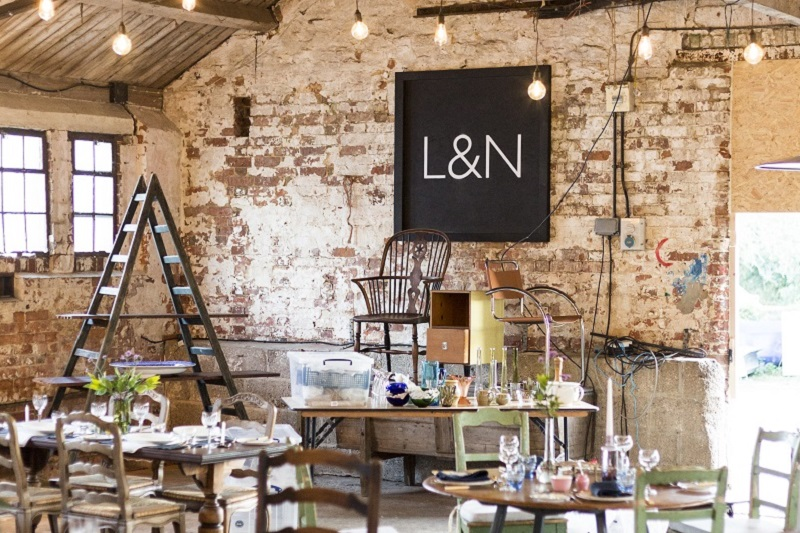 Lamb & Newt Pop-up Shop in a barn with sign on wall surrounded by vintage furniture