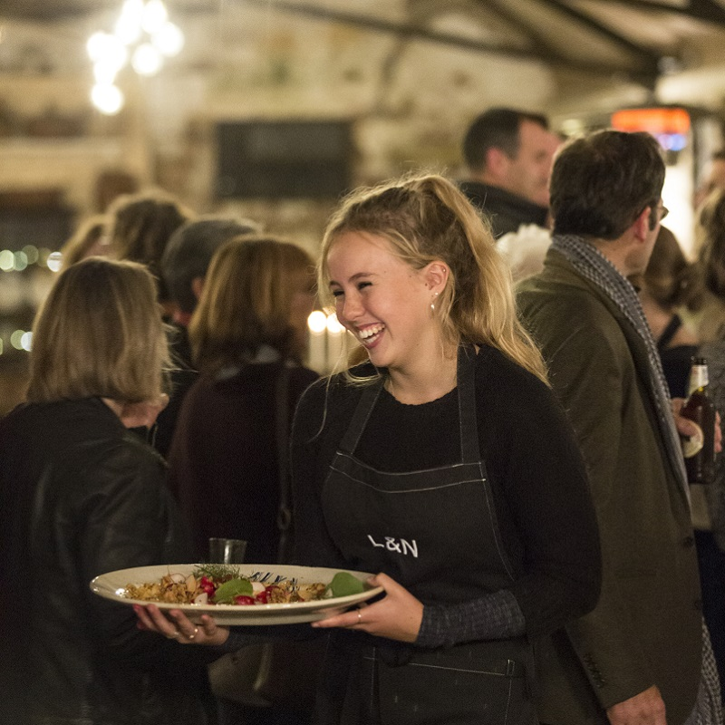Waitress smiling and serving at Lamb & Newt pop-up restaurant