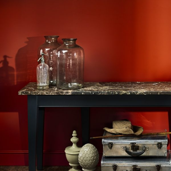 Side table with jars in front of Burnt Orange painted wall