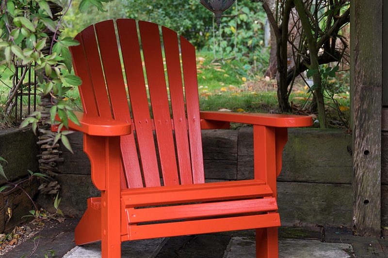 Burnt orange painted wooden chair in a garden corner