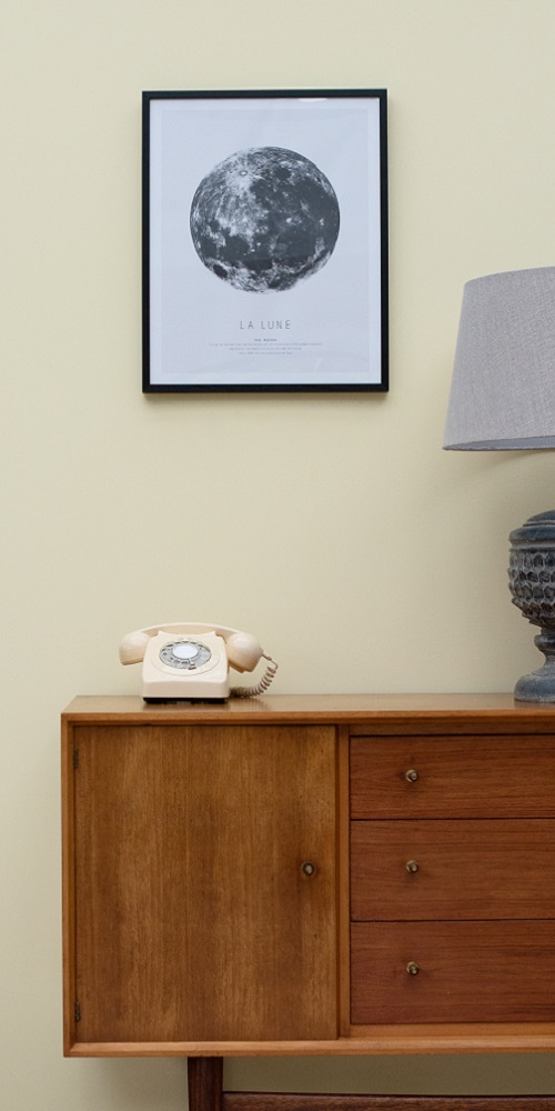 Yellow painted wall with wooden sideboard infront, an old telephone sits on top and a moon picture is hung in a frame above