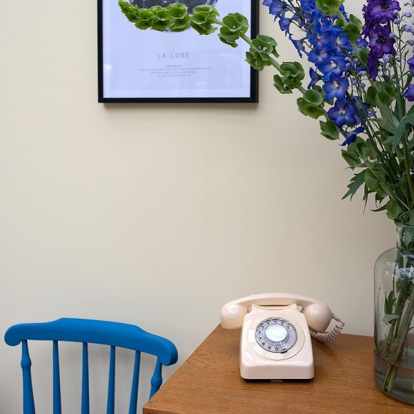 Cavendish Saxe Bleu chair in front of neutral wall, table with telephone