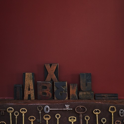 Dark red wall with wooden letters resting against it