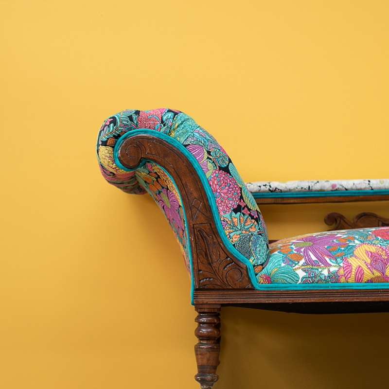 Antique floral sofa in front of yellow wall