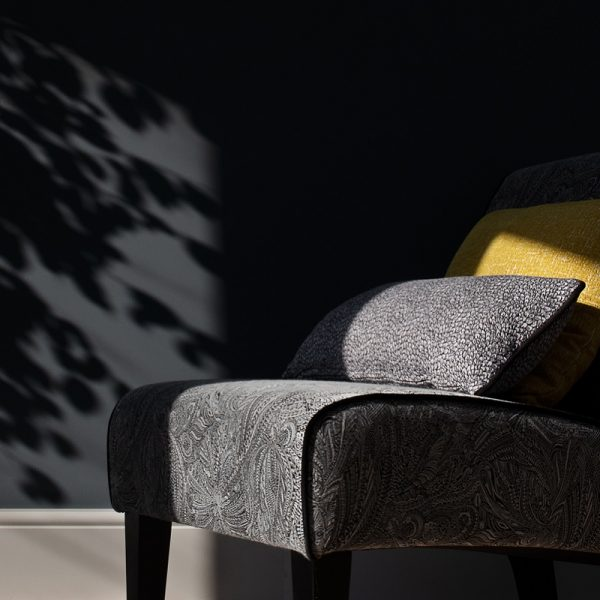 Grey chair with cushions in front of graphite painted wall