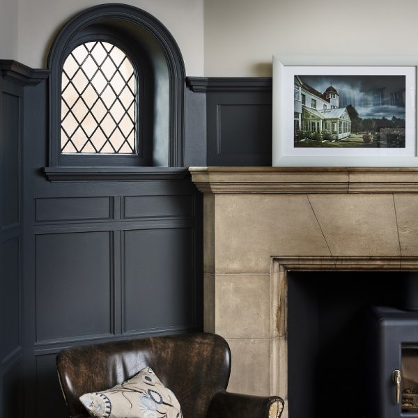 Living room with leather chair, fireplace and photography in front of grey wall