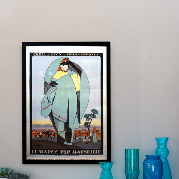 Vintage poster and a selection of blue vases in front of neutral wall