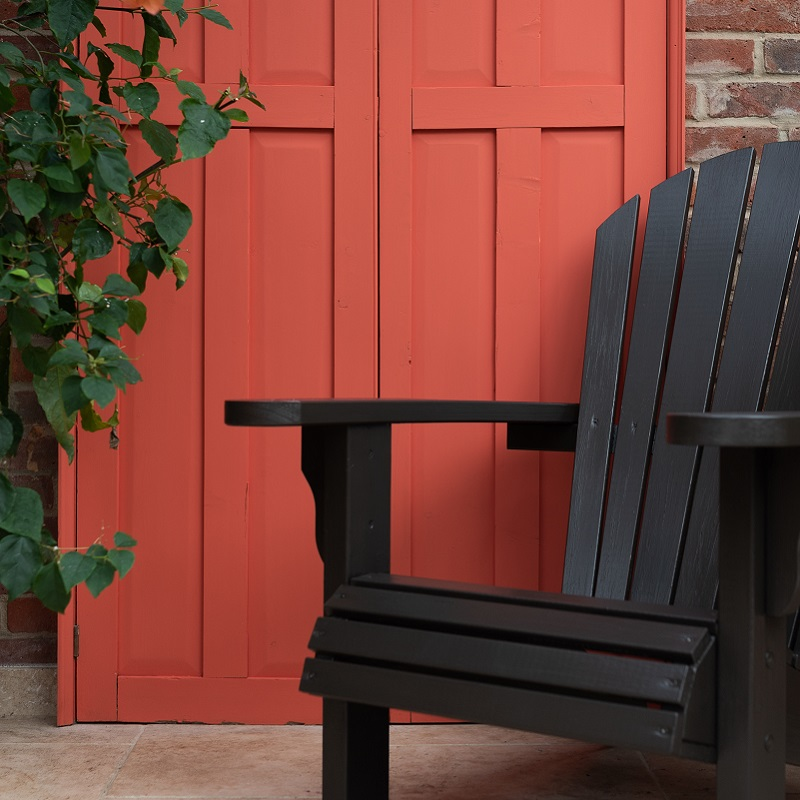 Black garden chair in front of red painted door