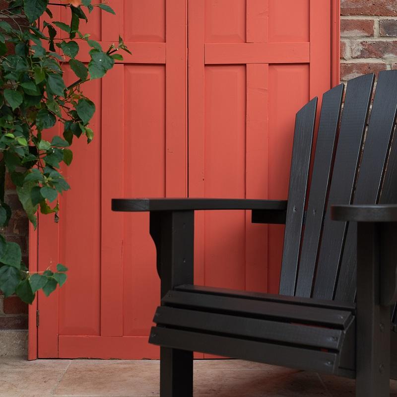 Black garden chair in front of red painted door