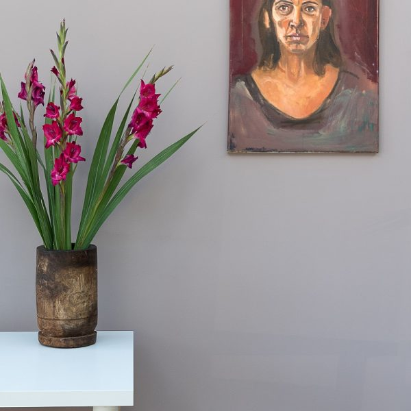Vase with pink and green flowers in front of a grey wall with painting