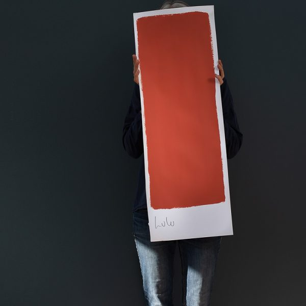 Person holding up a large colour card with Lulu red paint