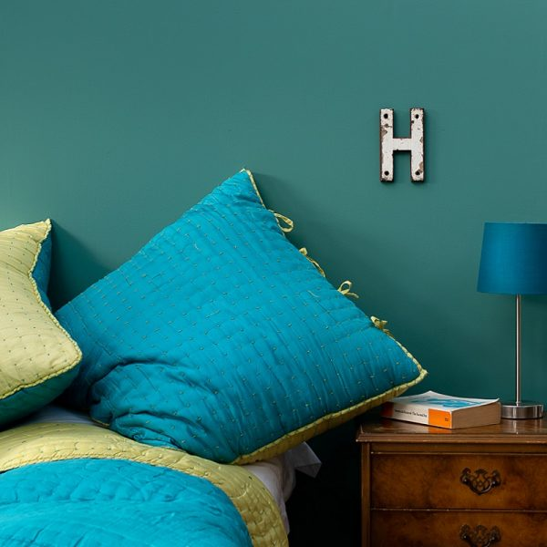 Turquoise bedding, bedside table and lamp in front of green wall
