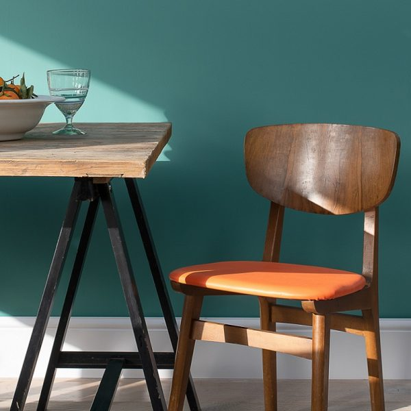 Dining table and chair in front of green wall