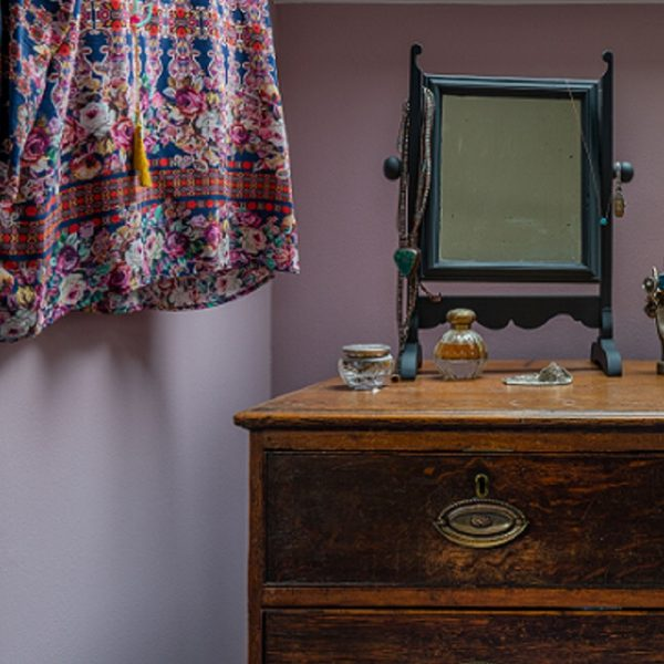 Chest of drawers with accessories and mirror in front of rose coloured wall