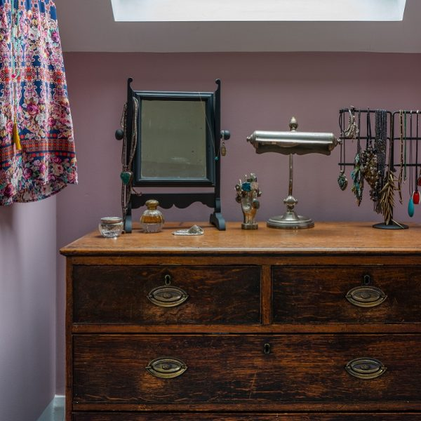 Chest of drawers with jewellery and mirror in front of rose coloured wall