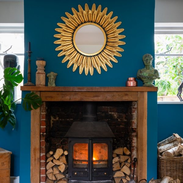 Lit fireplace with mantelpiece, firewood and large gold mirror on blue wall