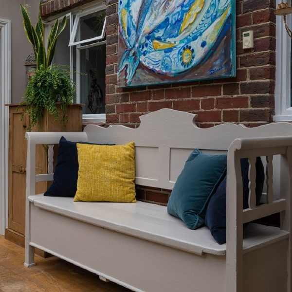 Painted bench with cushions in front of brick wall