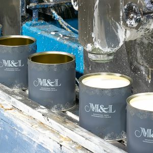 Paint tins at filling station being filled with M&L Primer