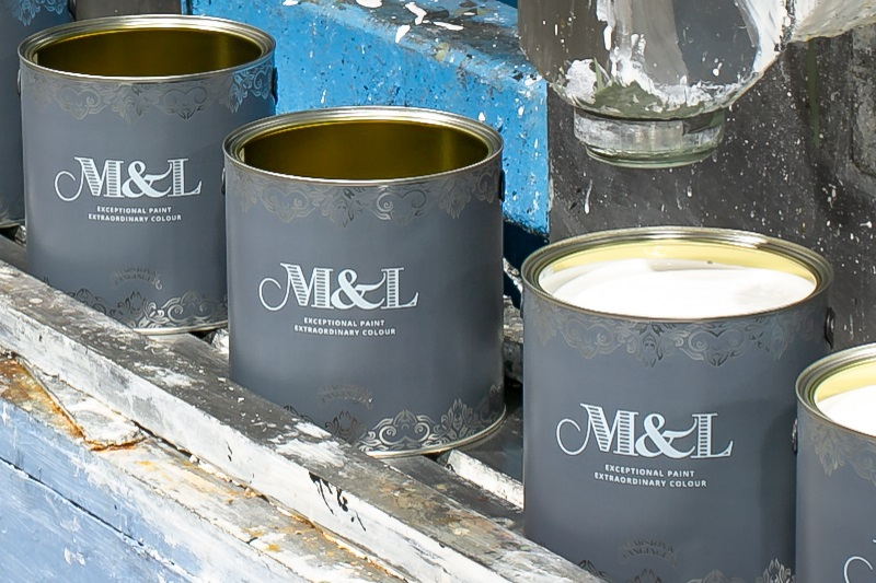 Paint tins in factory being filled with primer