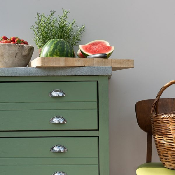 Green kitchen drawers, with chopping board and accessories on top