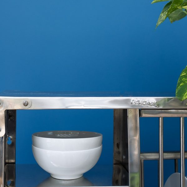Metallic kitchen bench with bowls in front of blue wall