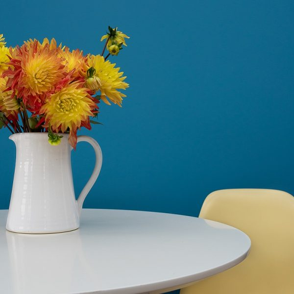 Ceramic jug with flowers on table in front of blue wall