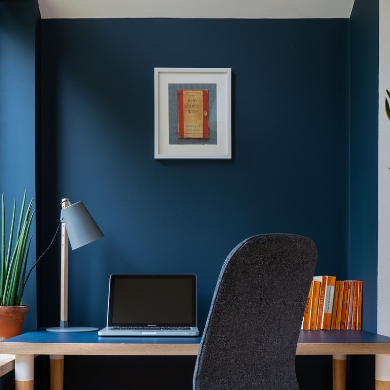 Office chair and desk with laptop, lamp and books in front of Smoke Blue coloured wall