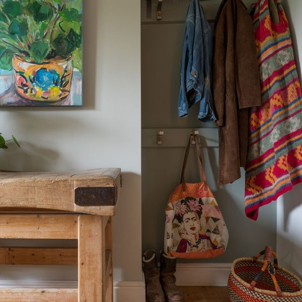 Coats on hangers with shoes, basket and wooden sideboard in front of green and grey walls