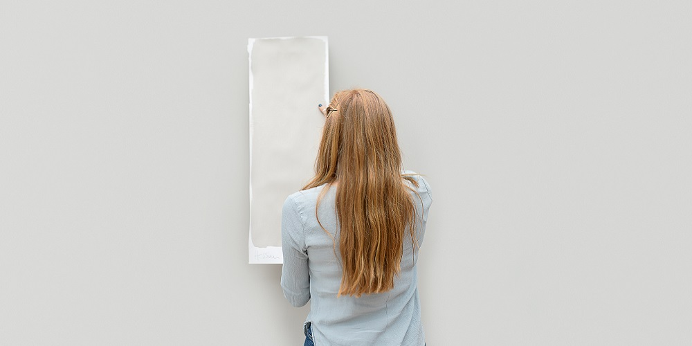 Girl with long hair holding a painted sheet against the same colour wall