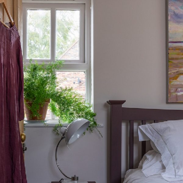 Red dress hanging on wooden door going into a lilac painted room with green plant on windowsill