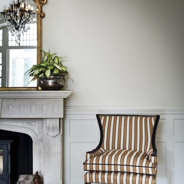Stripy yellow and white chair next to fireplance in front of white painted walls