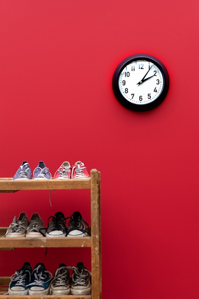 Wimpole poppy wall with shoe rack filled with converse. A clock sits on the wall at the top