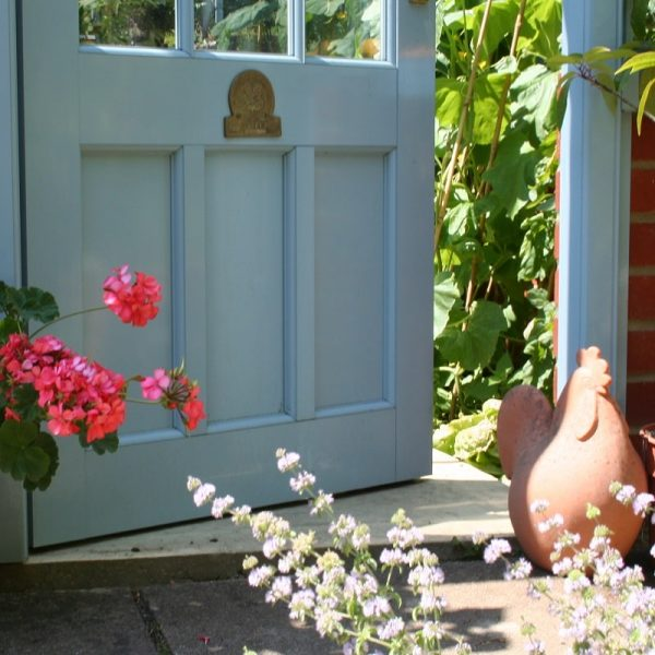 Chalkhill Blue door on a National Trust Scotney greenhouse, slightly ajar with some flowers in the foreground