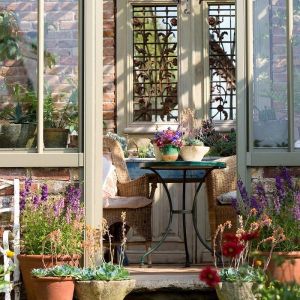 Through the door of an Alitex greenhouse painted in Greensand. Looking through to a table and chairs with pots of plants on the steps leading in and on the table