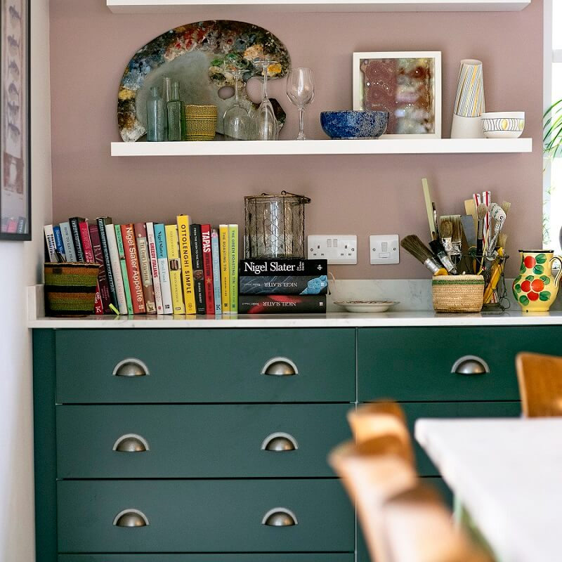 Corsican Green kitchen draws with old rose wall and pure white shelves